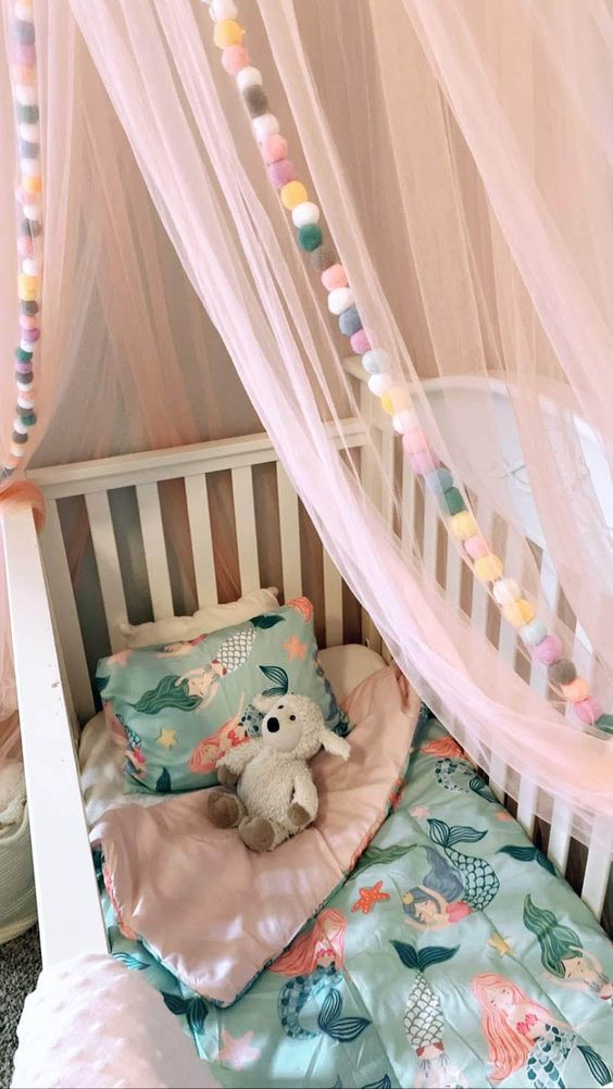 colorful pompom garlands and a light canopy to accent a baby's crib and make it cozier and welcoming