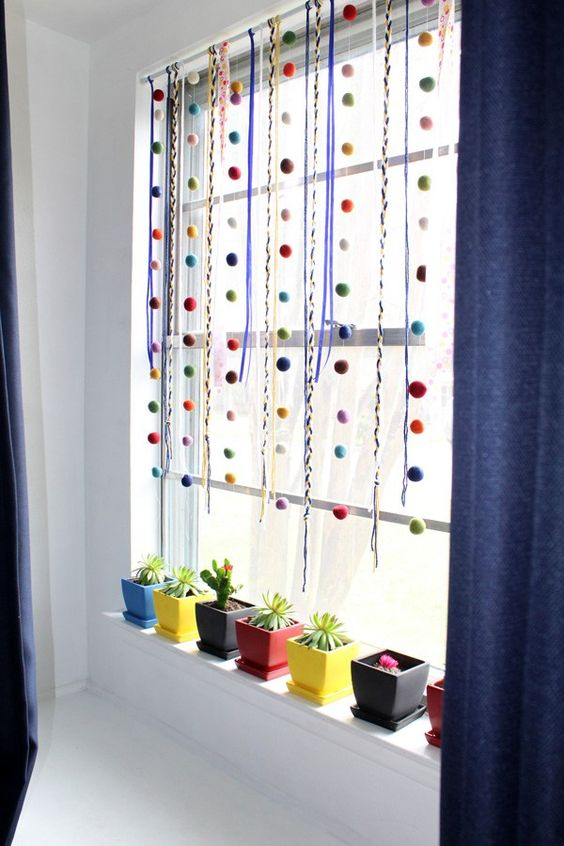 colorful ribbons and pompom garlands plus colorful planters to make the modern space very bold