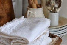 kitchen towels stored in a vintage dough bowl is a cool idea for a rustic kitchen