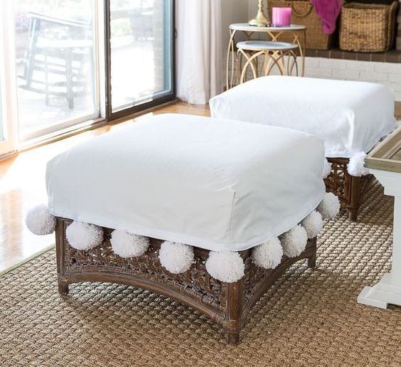 rattan ottomans with white covers and large white pompoms are amazing to give a chic feel to the space