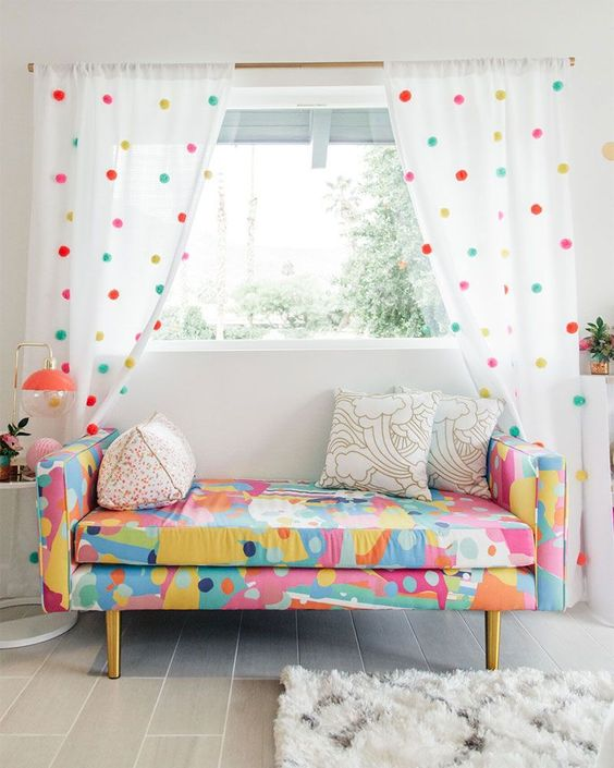 simple white curtains accented with colorful pompoms to match the loveseat