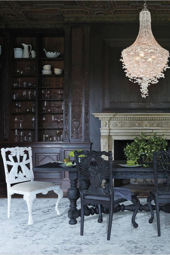 a Gothic dining room with black walls, a black table, black and white chairs, a white butterfly chandelier