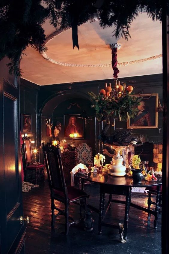 a Gothic dining room with black walls and a floor, a round table, chairs, artworks, candles and a fireplace