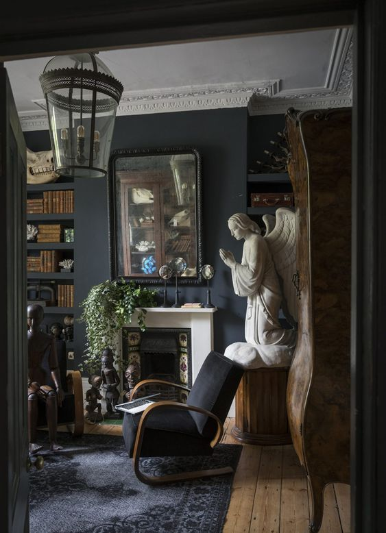 a Gothic living room with a tiled fireplace, molding, black furniure, unique artworks and greenery in pots
