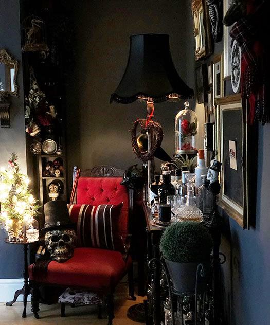a Gothic living room with black walls, a refined red chair, skulls and a chic gallery wall is striking