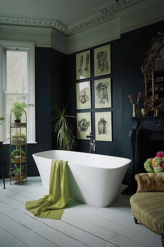 a Victorian Gothic bathroom with black walls and molding on the ceiling, a refined black fireplace, a modern tub, a grid gallery wall and lots of potted plants