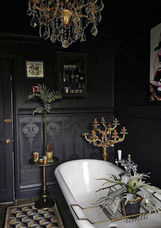 a beautiful black Gothic bathroom with black walls and black wallpaper, a black cabinet, a vintage bathtub, a crystal chandelier and candles