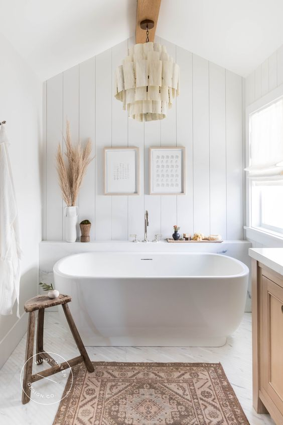 a beautiful boho bathroom with an oval tub, a beadboard wall, a wooden vanity, a fabric chandelier is very chic