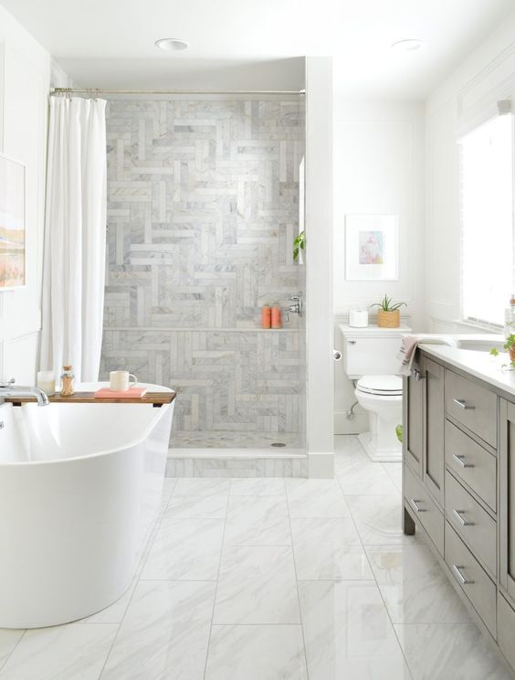 a beautiful farmhouse bathroom with various tiles, a grey vanity, a curtain and an oval tub plus white appliances
