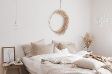 a beautiful modern boho bedroom with wooden furniture, a neon sign, a pampas grass wreath and neutral bedding