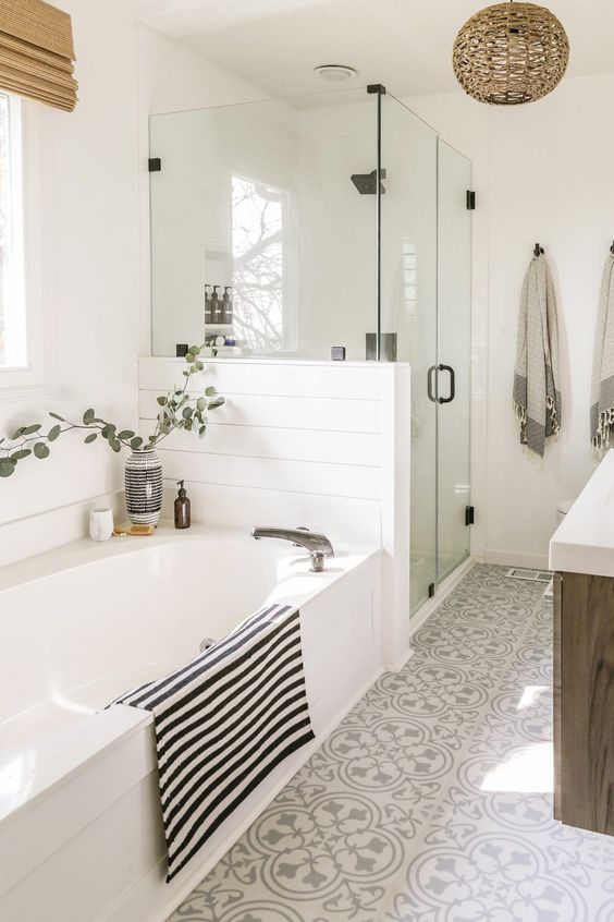 a boho neutral bathroom with beadboard, printed tiles, a wooden vanity, printed textiles, a woven lamp and a shower space