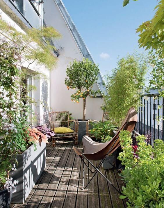 a bright and welcoming terrace with rattan and wicker chairs with bright upholstery, potted greenery and blooms