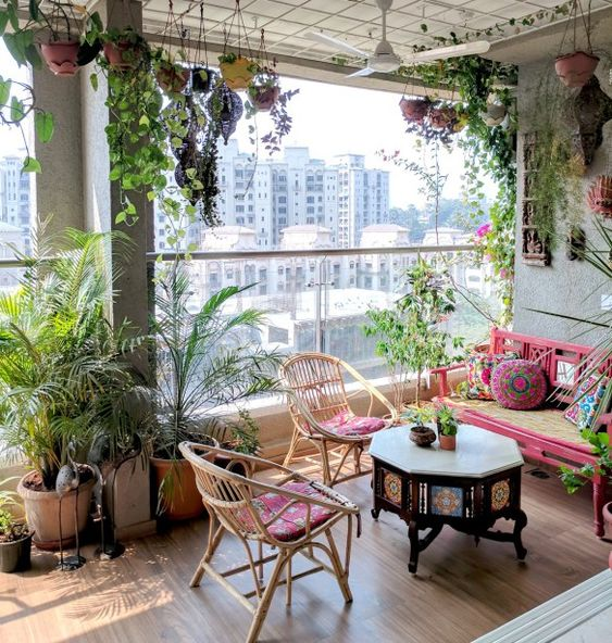 a bright boho terrace with rattan furniture and colorful upholstery, a carved wooden table, potted greenery everywhere