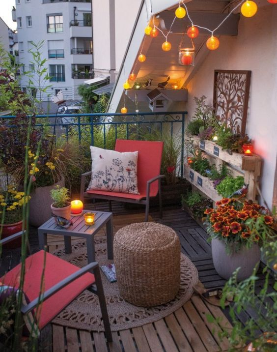 a bright eclectic terrace with a couple of chairs and side tables, a rug, lights and potted blooms and greenery