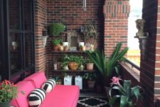 a bright small terrace with potted greenery and flowers, a bright pink sofa, patterned pillows and rugs