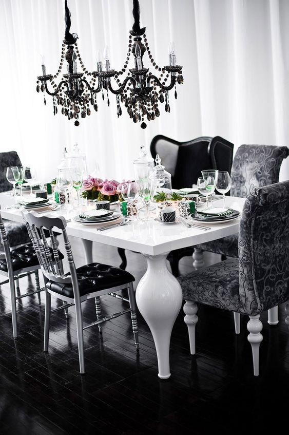 a catchy Gothic dining space with a white table with unique legs, black chairs and armchairs, black crystal chandeliers over the table