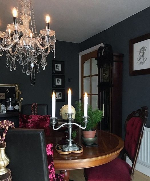 a chic Gothic kitchen with black walls, a round table, burgundy chairs, a crystal chandelier, potted greenery and artworks