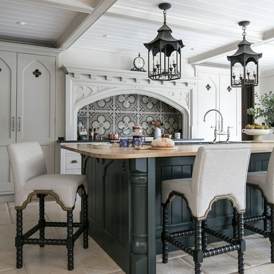 a chic Gothic kitchen with white cabinetry, a graphite grey kitchen island, neutral upholstered stools and catchy vintage lamps