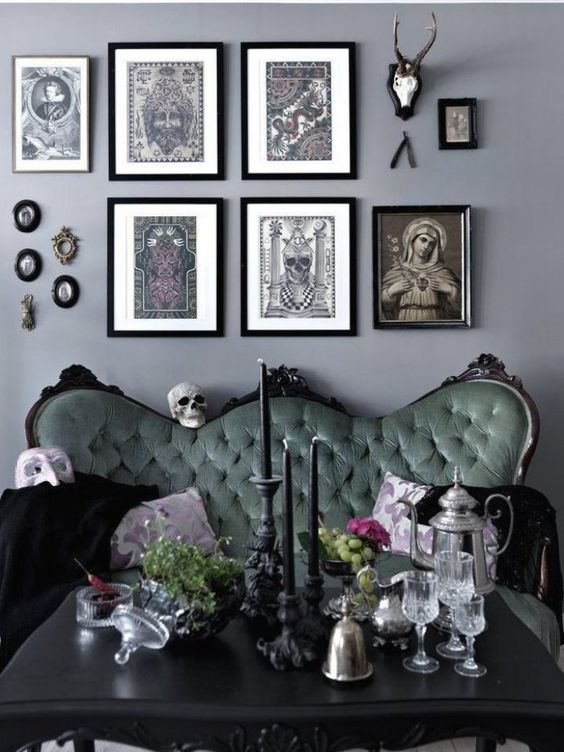 a chic Gothic living room with grey walls, a refined green sofa, a black table and a catchy gallery wall and candles