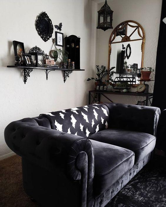 a chic Gothic living room with white walls, dark furniture, a shelf with cool objects on display and potted greenery