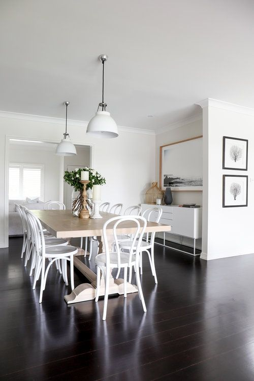 a chic dining room with a long vintage-inspired table, white chairs, white pendant lamps, a chic credenza and a large artwork