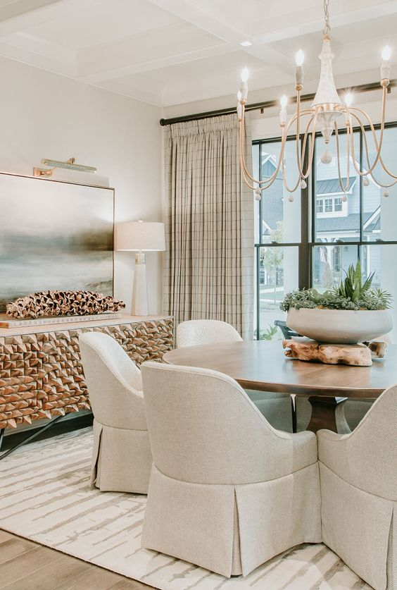 a chic neutral dining room with a stained round table, neutral chairs, a beautiful chandelier, a jaw-dropping credenza