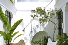 a chic terrace with butterfly furniture, potted greenery, a mobile hearth and much natural light