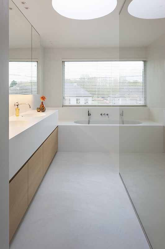 a clean minimalist bathroom with a built-in bathtub, a large vanity and built-in sinks, a large window with shutters