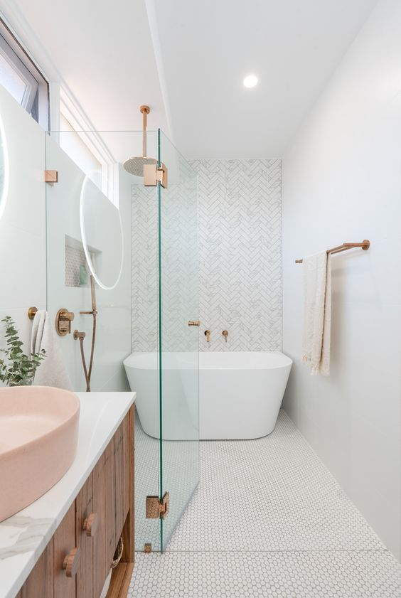 a contemporary bathroom with penny and herringbone tiles, a free standing tub, a wooden vanity and a pink sink and brass touches