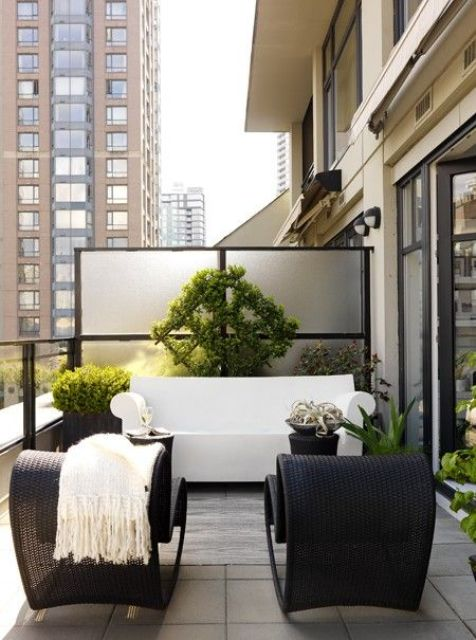 a contemporary monochromatic terrace with black wicker chairs, a white sofa, lots of potted greenery