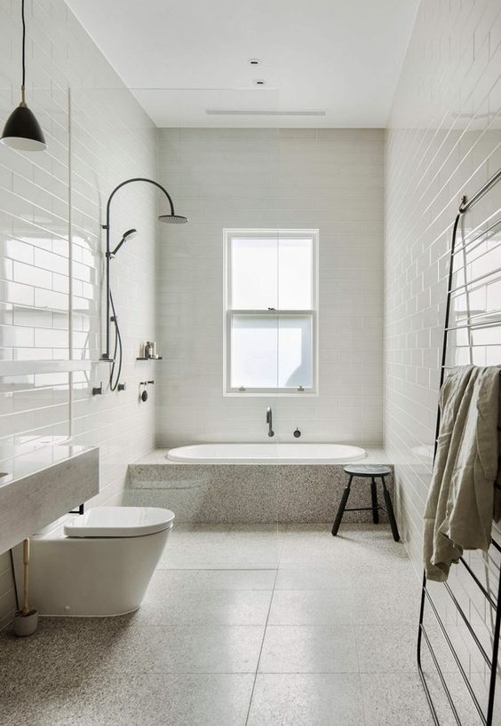 a contemporary neutral bathroom with mismatching tiles, a bathtub clad with stone and white appliances plus black touches
