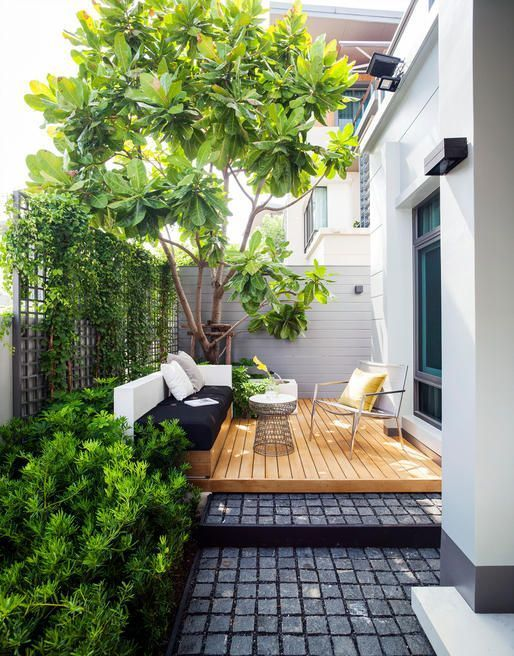 a contemporary terrace with a built in bench in black and white, a deck, a comfy chair and a coffee table
