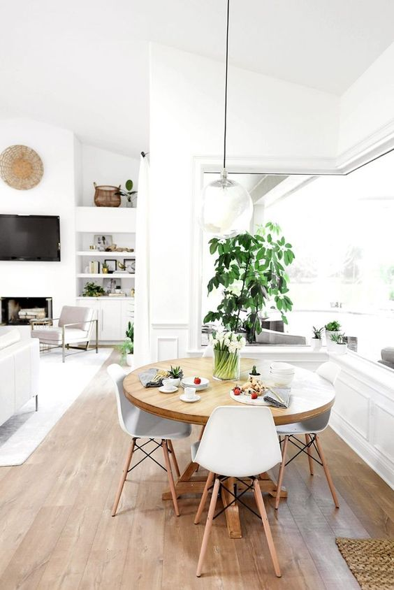 a cool neutral dining space with a corner window, a round table, white chairs, potted greenery and a pendant lamp