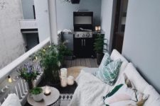 a cozy boho terrace with a white sofa, bright pillows and a blanket, a side table with potted greenery and blooms plus a grill