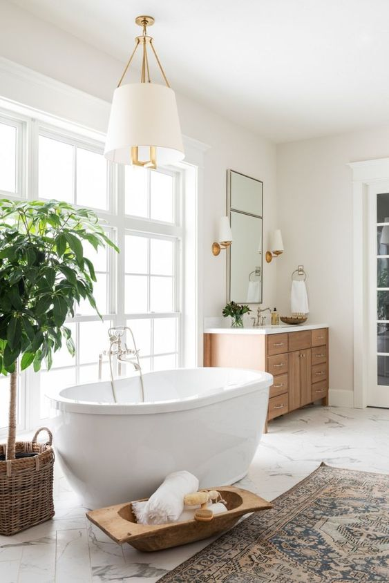 a cozy neutral bathroom with a marble floor, an oval tub, a wooden vanity and a potted tree plus elegant lamps