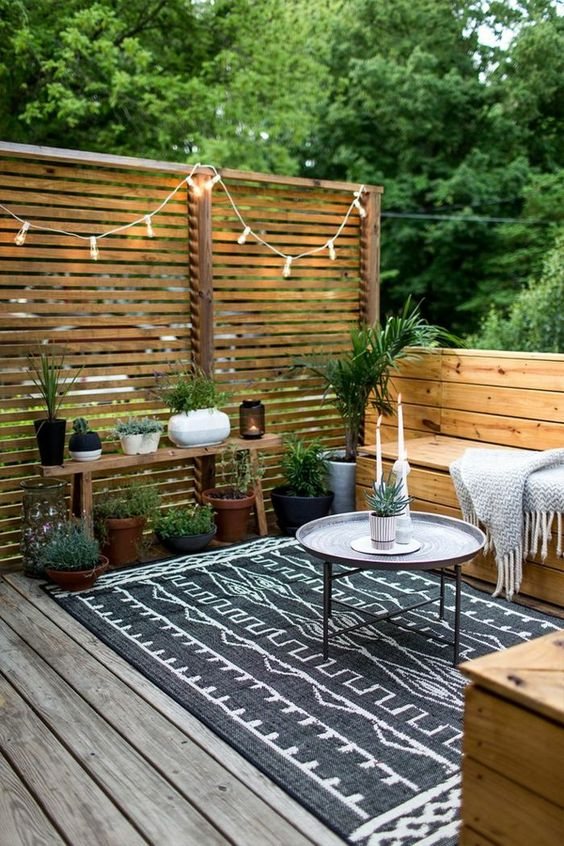 a cozy small terrace with wooden furniture, a small coffee table, a boho rug, potted greenery and lights