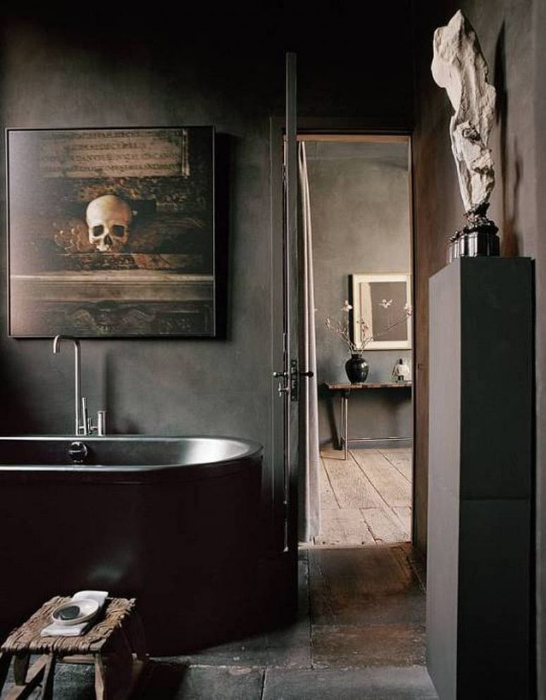 a delicate Gothic bathroom in black, with concrete walls, a stone tub, a rough wooden stool and a beautiful vintage artwork