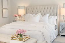 a glam and vintage neutral bedroom with a creay bed, a crystal chandelier, a neutral bench, mirrors and artworks