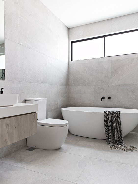 a grey minimalist bathroom clad with large scale tiles, an oval tub, a long and narrow window and a floating vanity