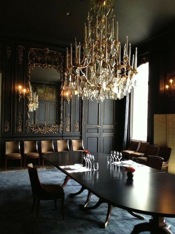 a jaw-dropping Gothic dining room with black and gold paneled walls, a large mirror, an oval table, upholstered chairs and a fantastic chandelier