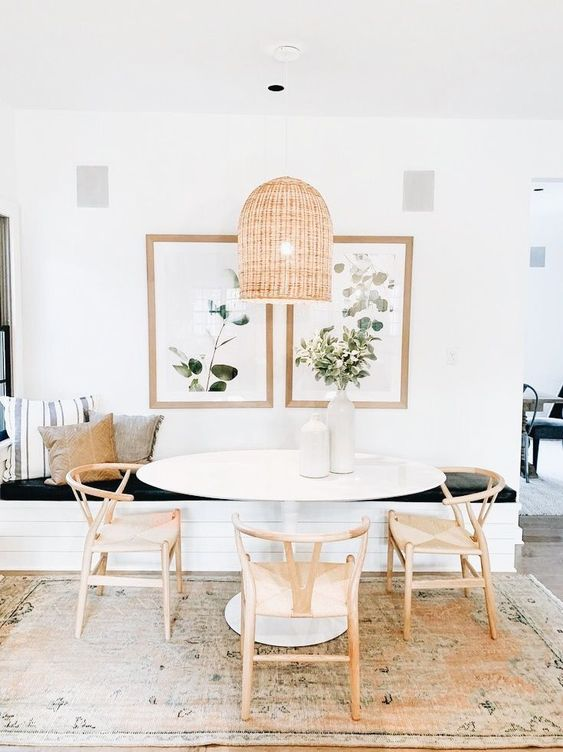 a lovely modern farmhouse dining room with a built-in bench, an oval table and wooden chairs, a woven pendant lamp