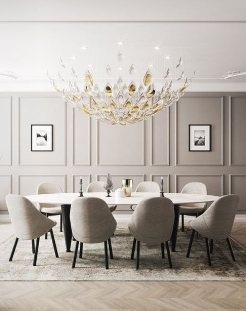 a luxurious dining space with a grye paneled wall, a large beautiful chandelier, a long oval table and grey upholstered chairs
