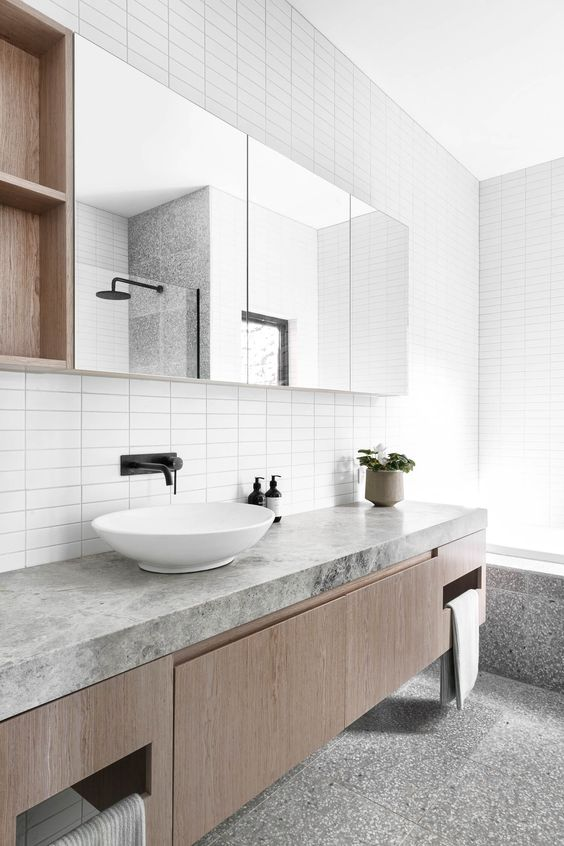 a minimalist grey and white bathroom with a floating vanity with a stone countertop, a mirror with storage compartments and a bathtub