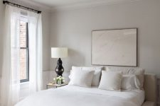 a minimalist neutral bedroom with an upholstered bed, neutral bedding, a retro chandelier and a statement artwork