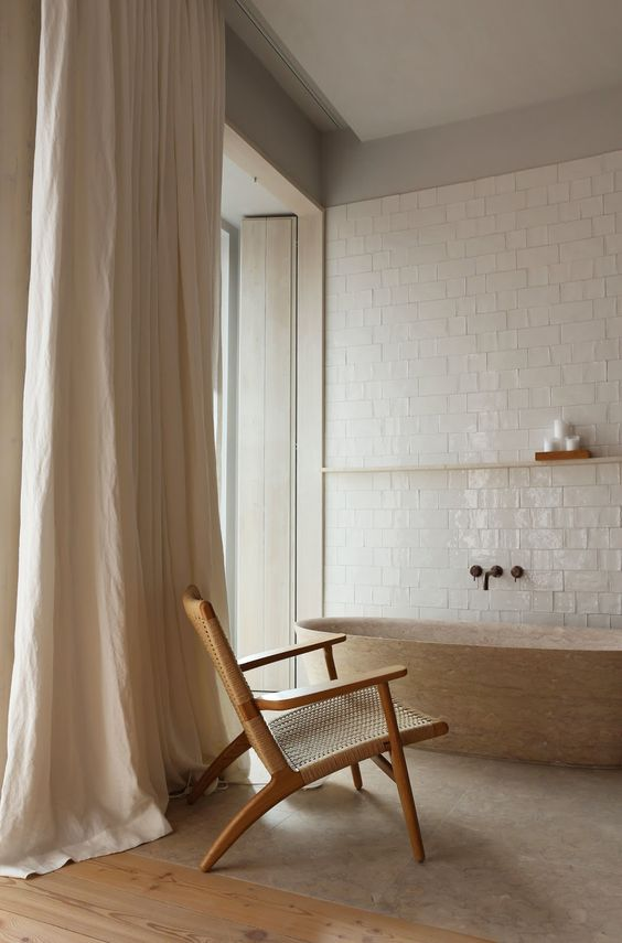 a minimalist yet warm bathroom with glossy white tiles, a wooden bathtub, a rattan chair and neutral curtains on the windows