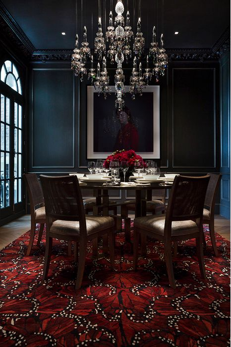 a modern Gothic dining room with black paneled walls, a glass table and upholstered chairs, a red carpet and a crystal chandelier