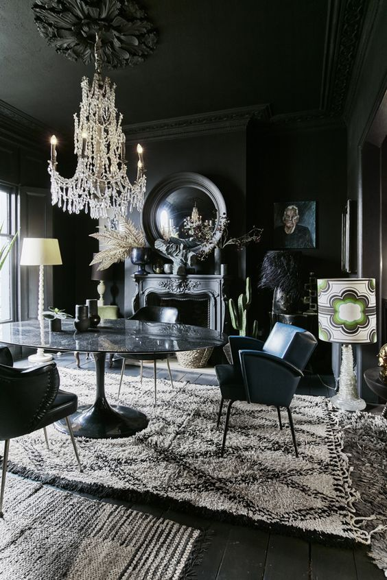 a modern Gothic dining room with black walls, floos and a ceiling, a stone table, leather chairs, mirrors, artworks and a refined chandelier