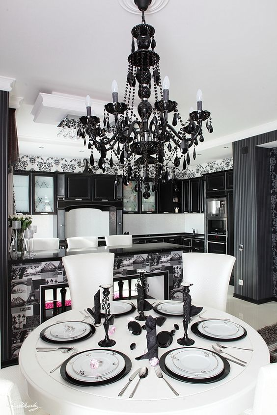a modern Gothic eat-in kitchen with black cabinetry, a print tile kitchen island, a large black crystal chandelier and a white table and chairs