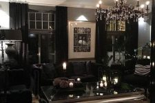 a modern Gothic glam living room with grey walls, black curtains and furniture, a crystal chandelier and candles