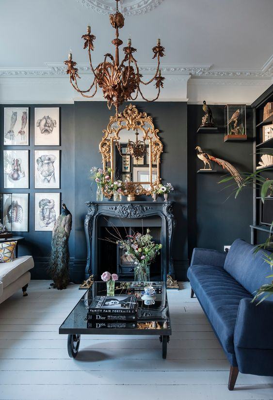 a modern Gothic living room with black walls, ablue and white sofa, a fireplace, a refined chandelier and mirror, catchy artworks